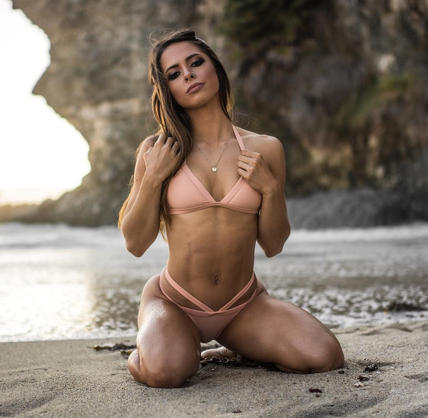 Jade Douglas-Hiley kneeling in the sand posing for a photo in her bikini