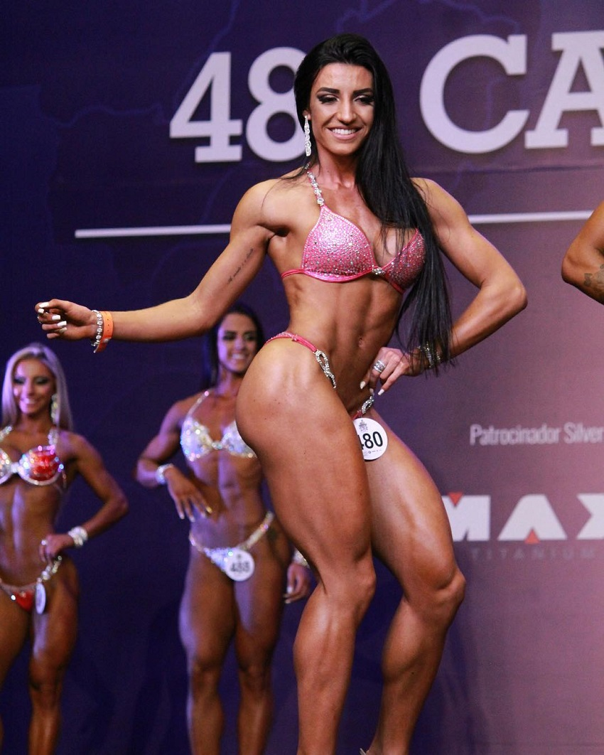 Jessica Basso Ortiz smiling and posing on the fitness stage looking ripped