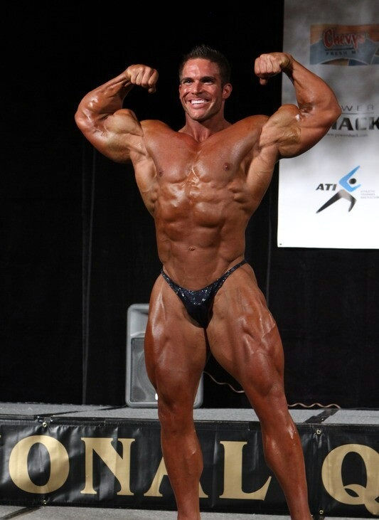 Josh Bergeron doing a front double biceps flex in front of the judges on a bodybuilding stage