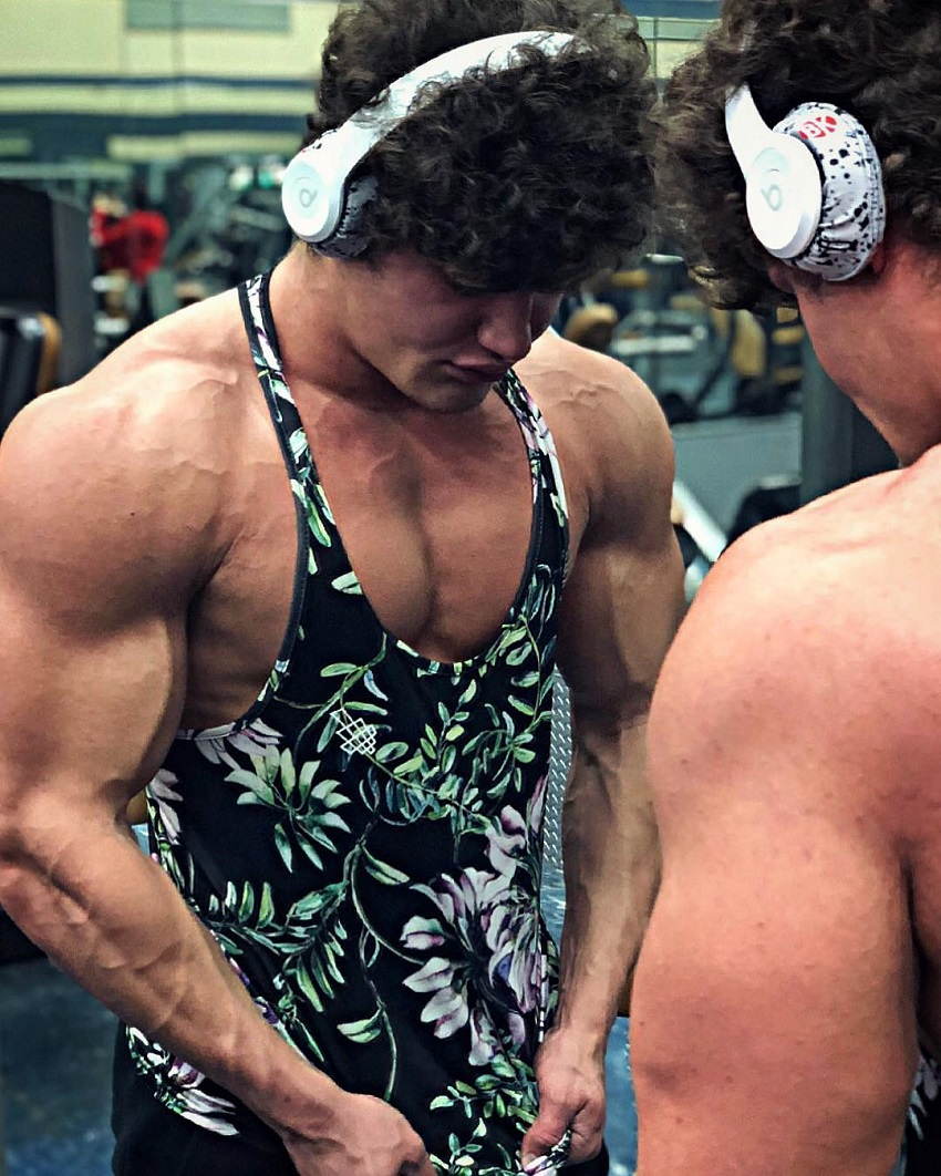 Justin Martilini standing in a gym by a mirror wearing white headphones getting 'pumped' for a workout