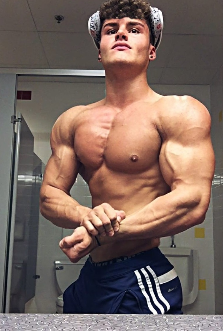 Justin Martilini performing a side chest pose for a photo looking lean and muscular