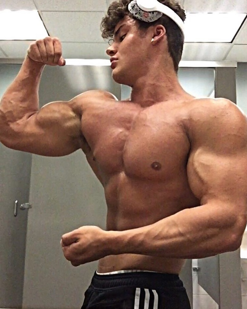 Justin Martilini standing shirtless flexing his bulging biceps in a photo