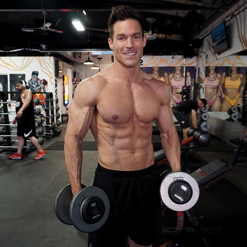 Kyle Clarke standing shirtless in the gym holding dumbbells in his hands