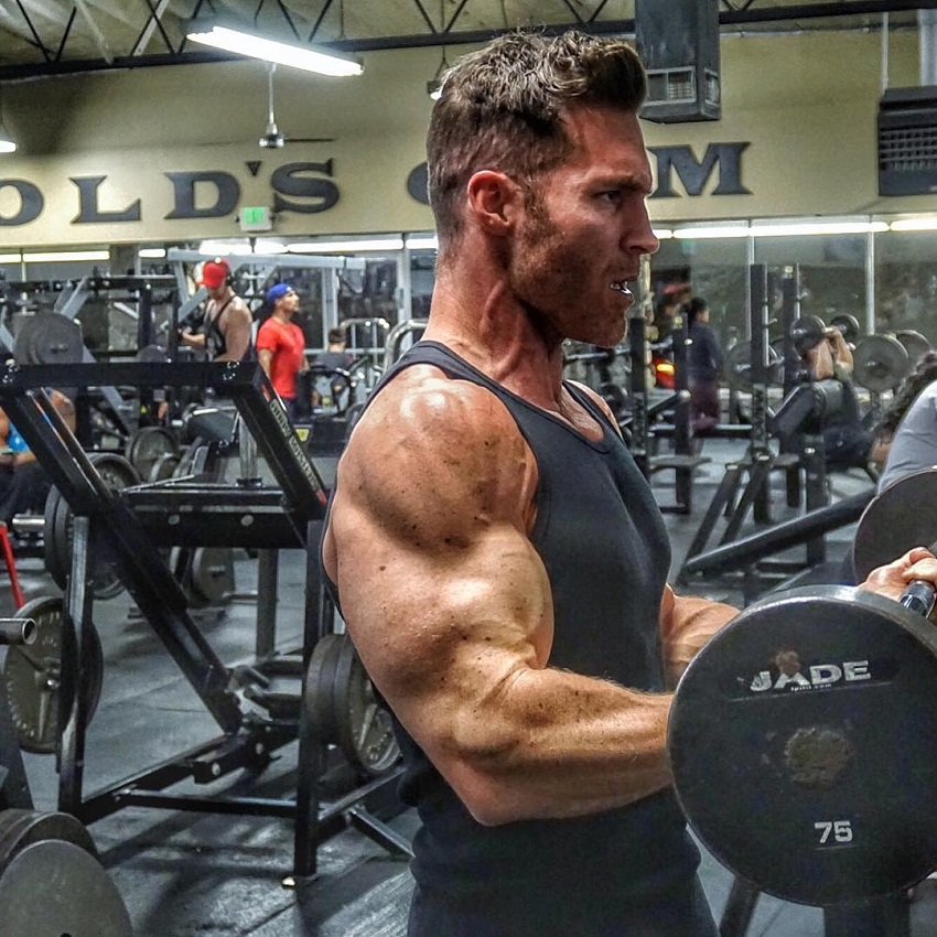 Kyle Clarke performing heavy barbell curls, his arms looking huge and ripped