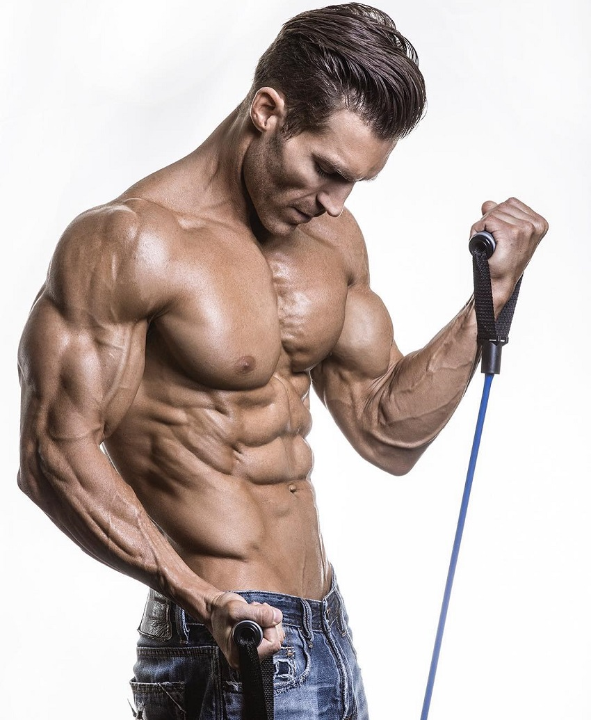 Kyle Clarke performing resistance band bicep exercise in a photo shoot, showing off his ripped and muscular body