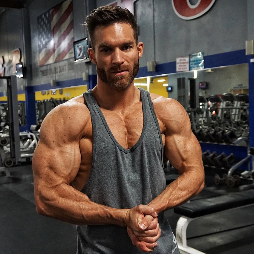 Kyle Clarke flexing his ripped muscles in a grey tank top