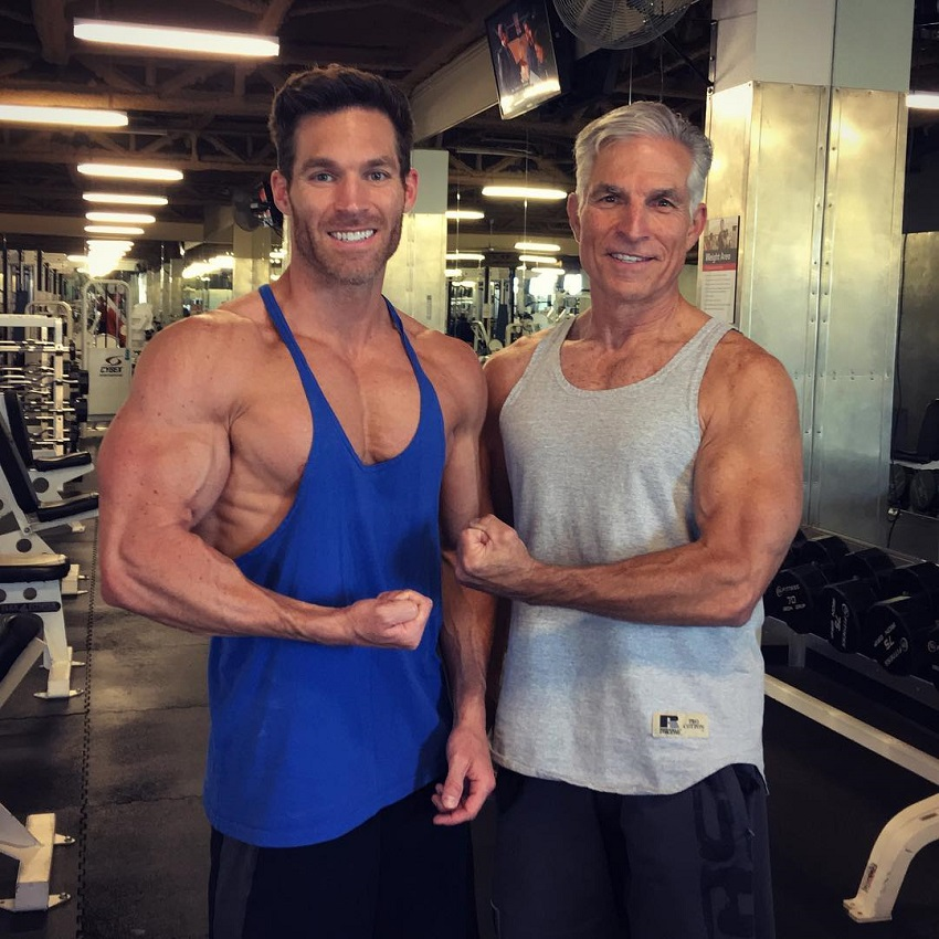 Kyle Clarke flexing his biceps with his dad