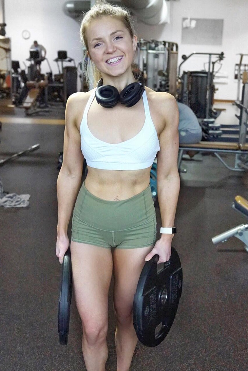 Lauren Tickner holding weight plates and smiling for a photo in a gym
