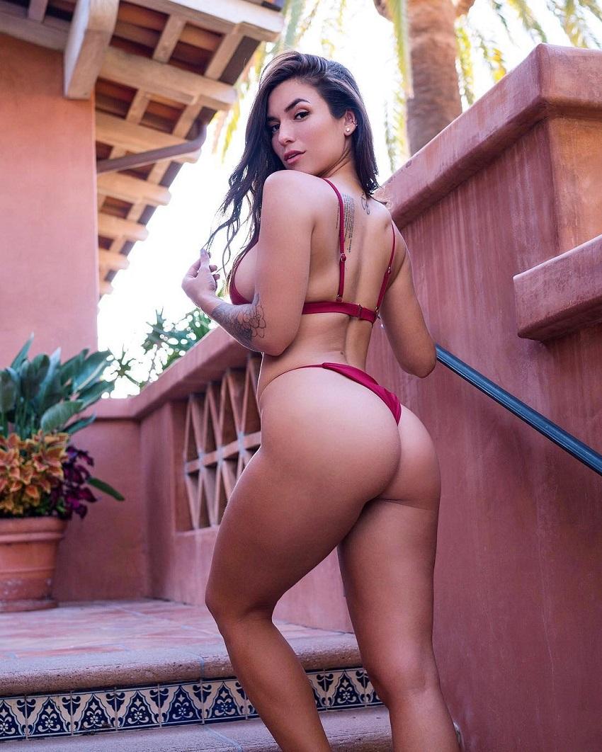 Luciana Del Mar posing in a red bikini showcasing her curvy glutes
