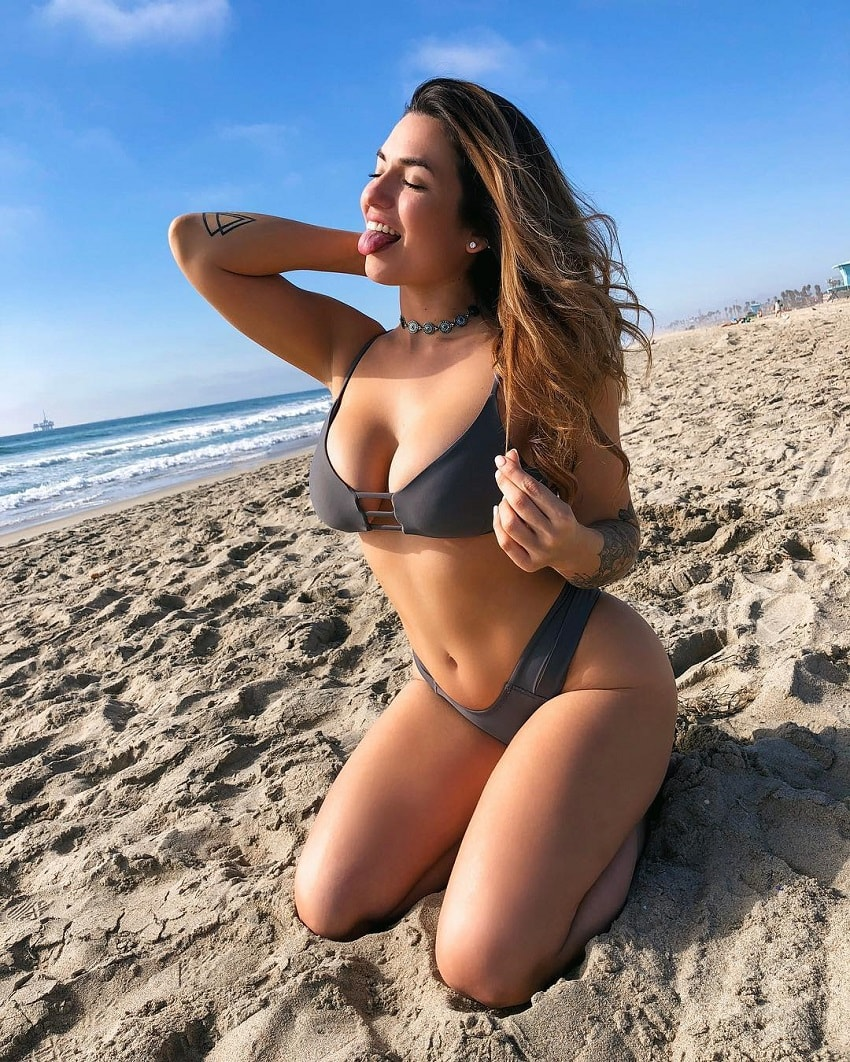Luciana Del Mar kneeling on the sand on the beach looking fit and curvy