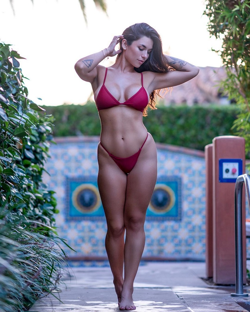 Luciana Del Mar wearing a red bikinig walking down the street looking lean and fit