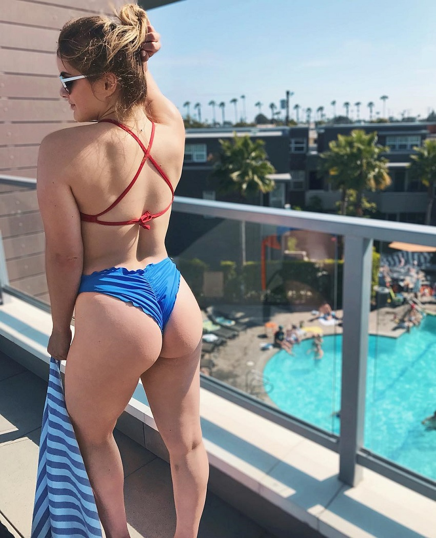 Marie Wold posing on the balcony overlooking a big pool looking fit and lean