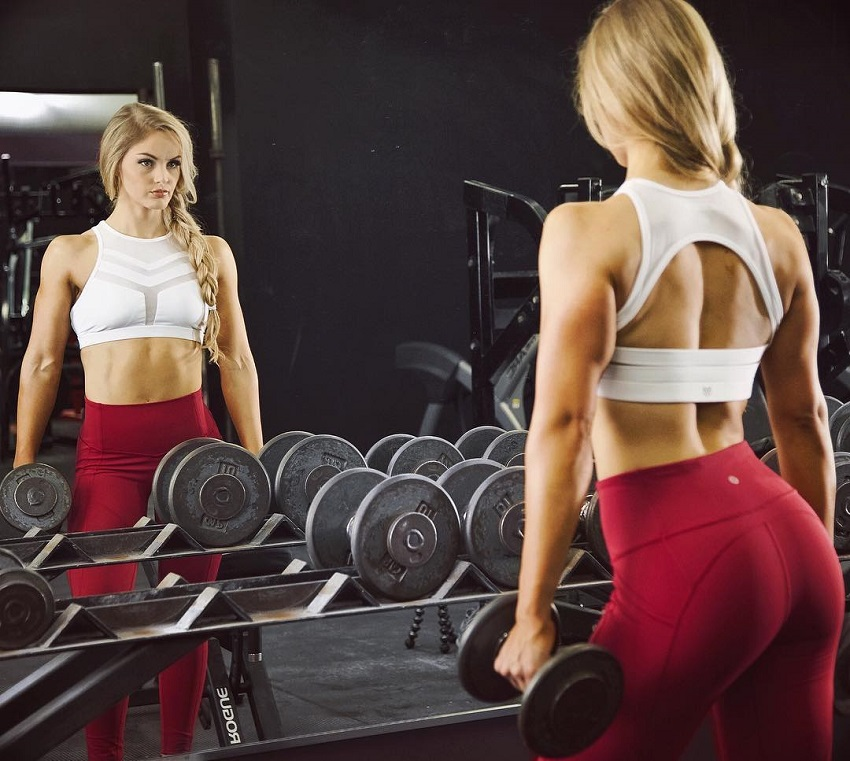 Marie Wold looking at herself in a mirror wearing red leggings and holding dumbbells in her hands