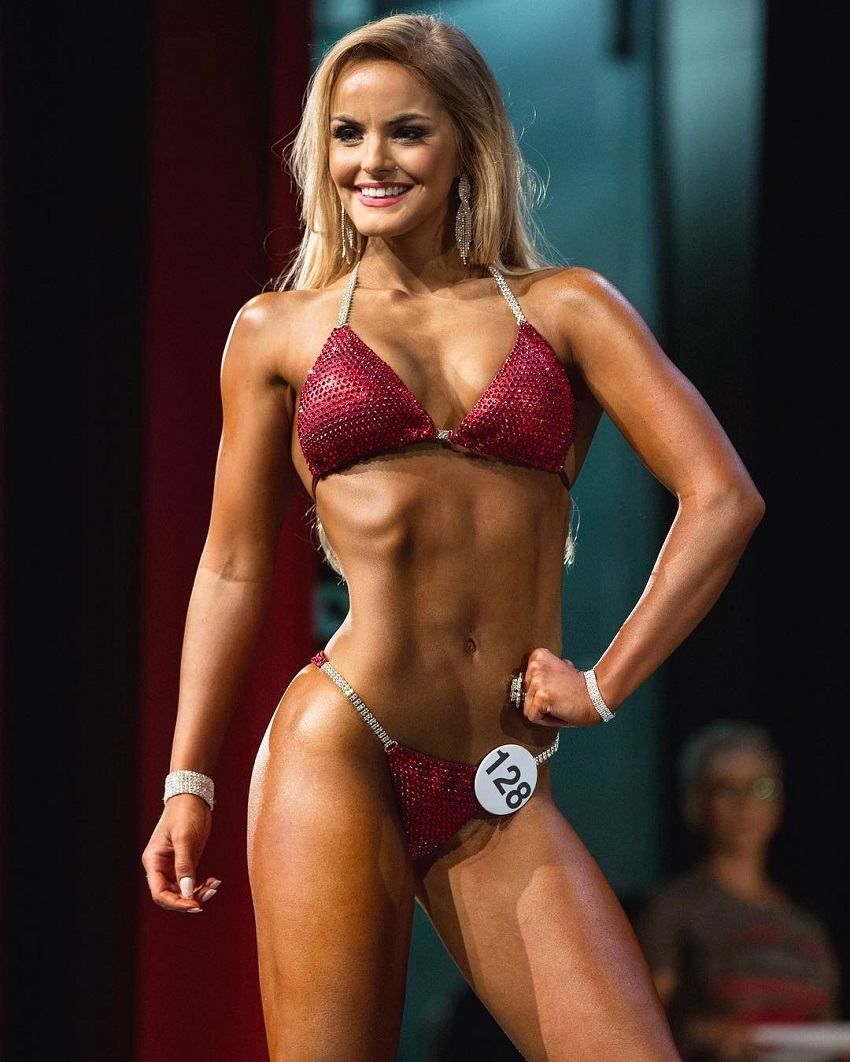 Marie Wold posing on a bikini stage looking fit and lean