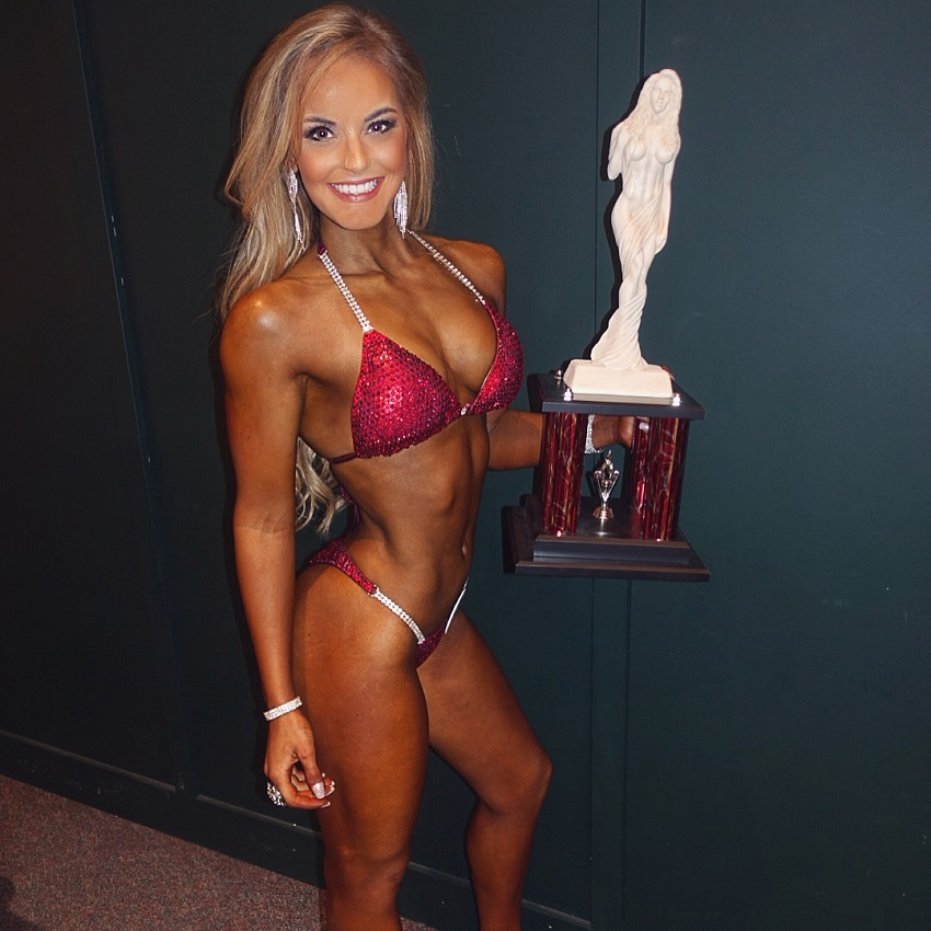 Marie Wold holding a trophy in her hands wearing a red bikini looking lean and fit