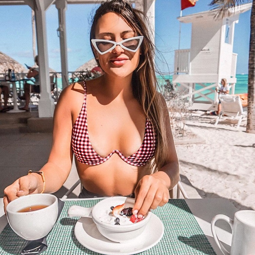 Michele Sullivan sitting in a chair outdoors in her bikini eating a healthy meal