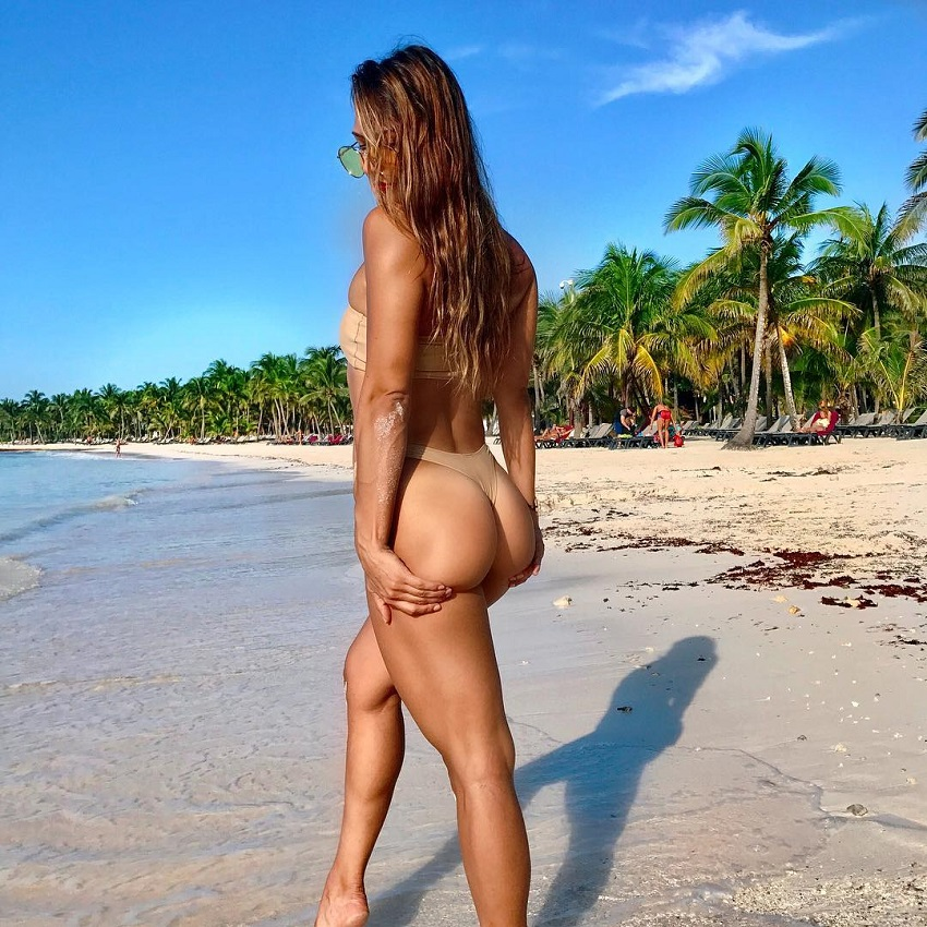 Michele Sullivan standing on a beach showing off her curvy glutes