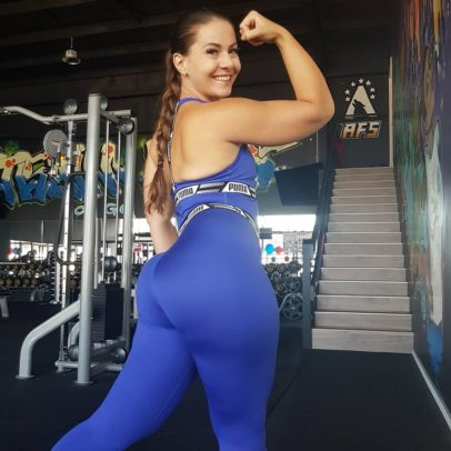 Monique de Dios flexing her biceps for a photo wearing blue leggings looking fit and curvy