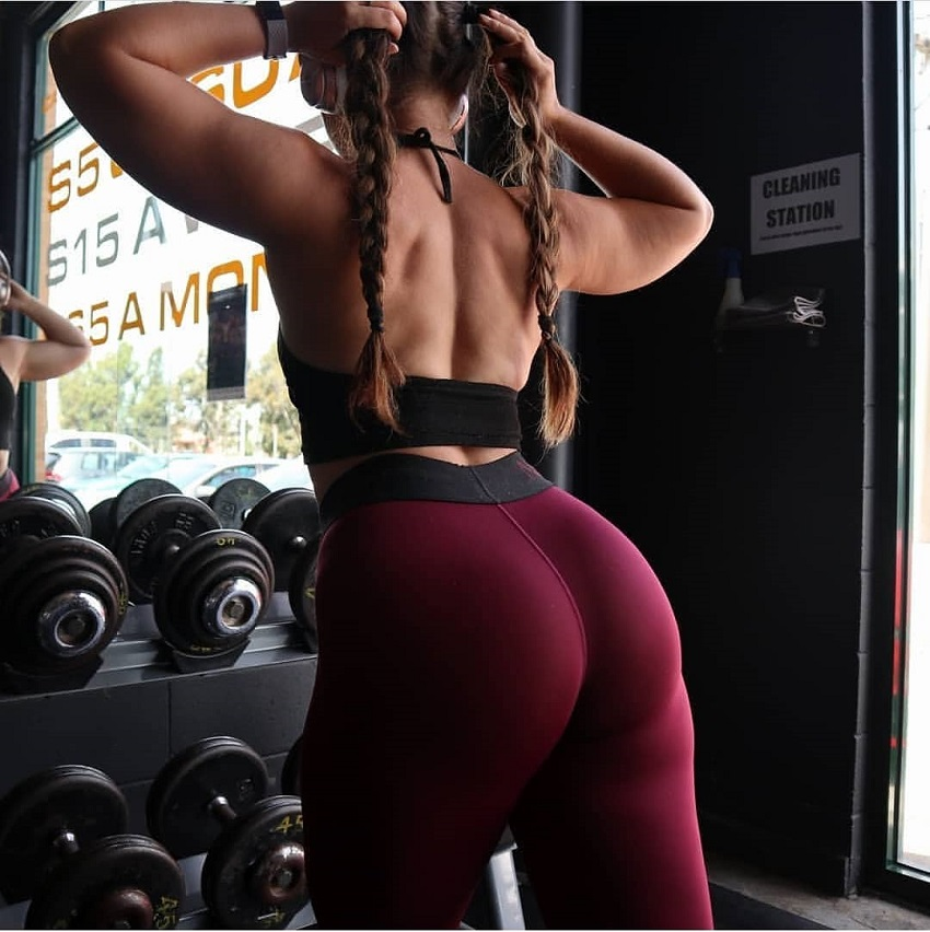 Monique de Dios posing by the dumbbell rack in the gym looking fit