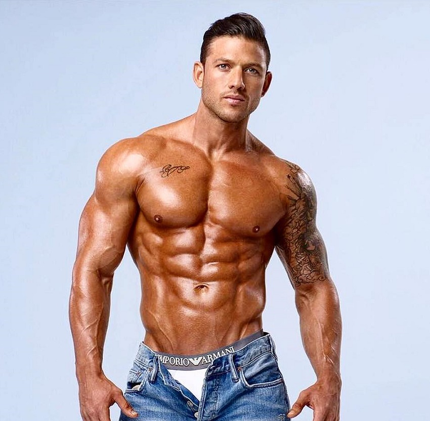 Rob Sharpe posing shirtless in a photo shoot looking muscular and ripped