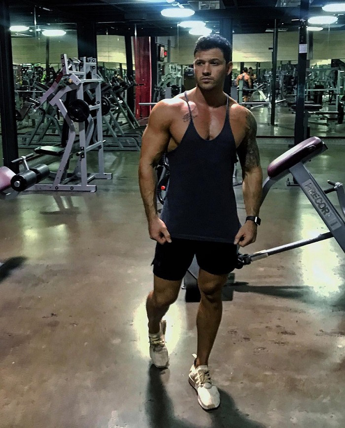 Rob Sharpe standing in a gym wearing a black tank top looking big and ripped