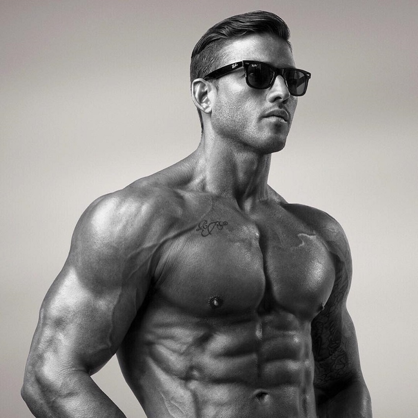 Rob Sharpe posing shirtless with sunglasses on, looking fit and lean