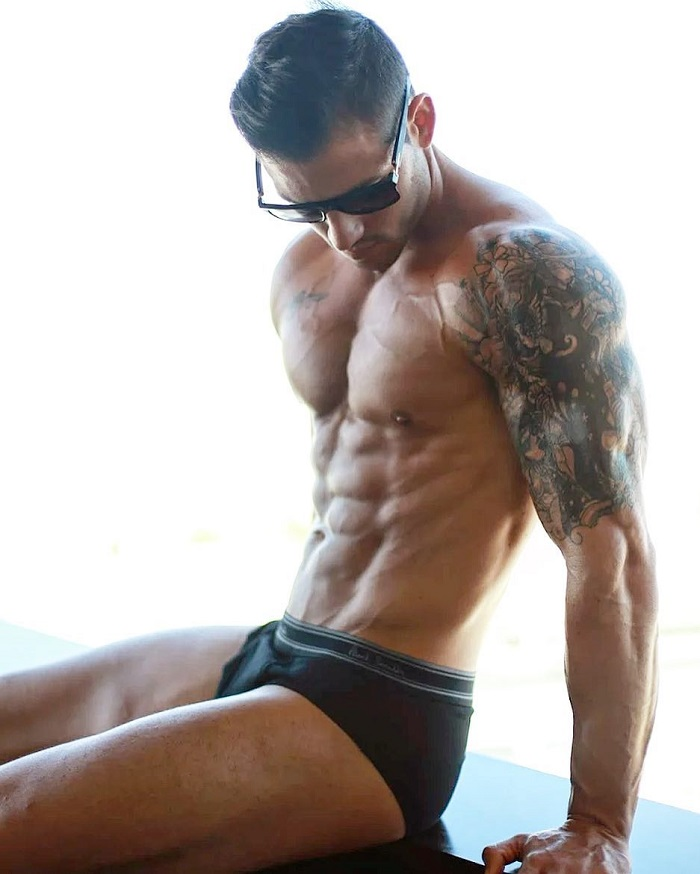 Rob Sharpe posing shirtless in a photo looking big and muscular with a tattoo on his arms and shoulders