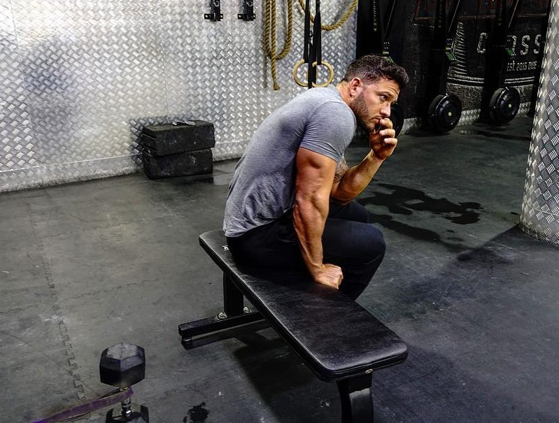 Rob Sharpe sitting on a bench showing off his ripped and muscular triceps
