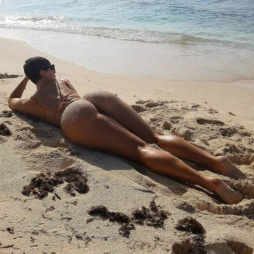 Zahra Elise lying on a sand beach looking aesthetic and curvy
