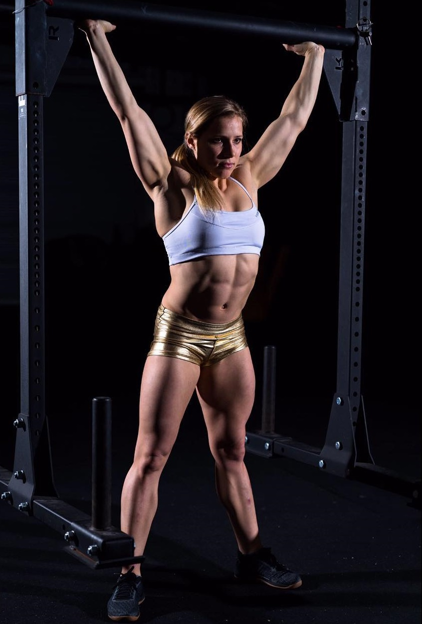 Alexis Johnson lifting dumbbells in a photo shoot showing off her lean midsection