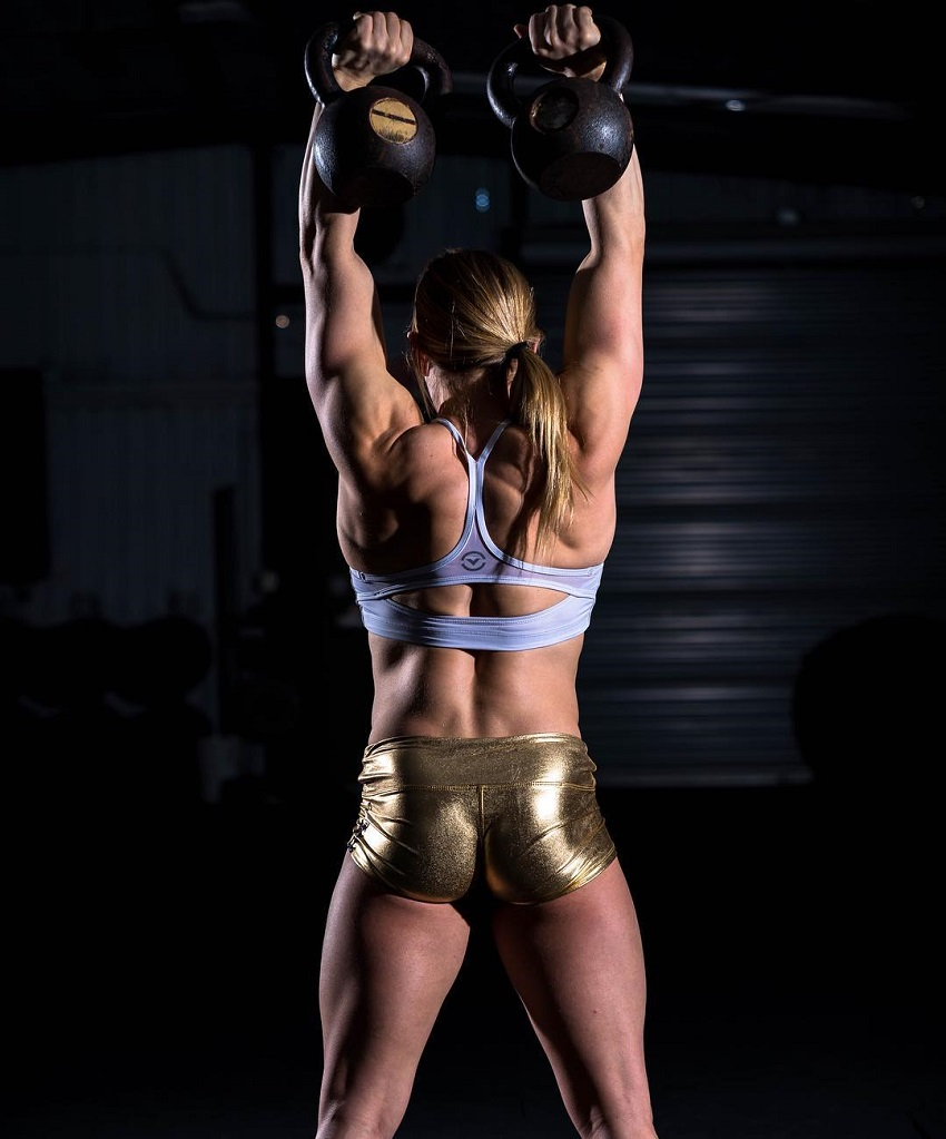 Alexis Johnson lifting kettlebells during a photo shoot,, showing off her amazing back