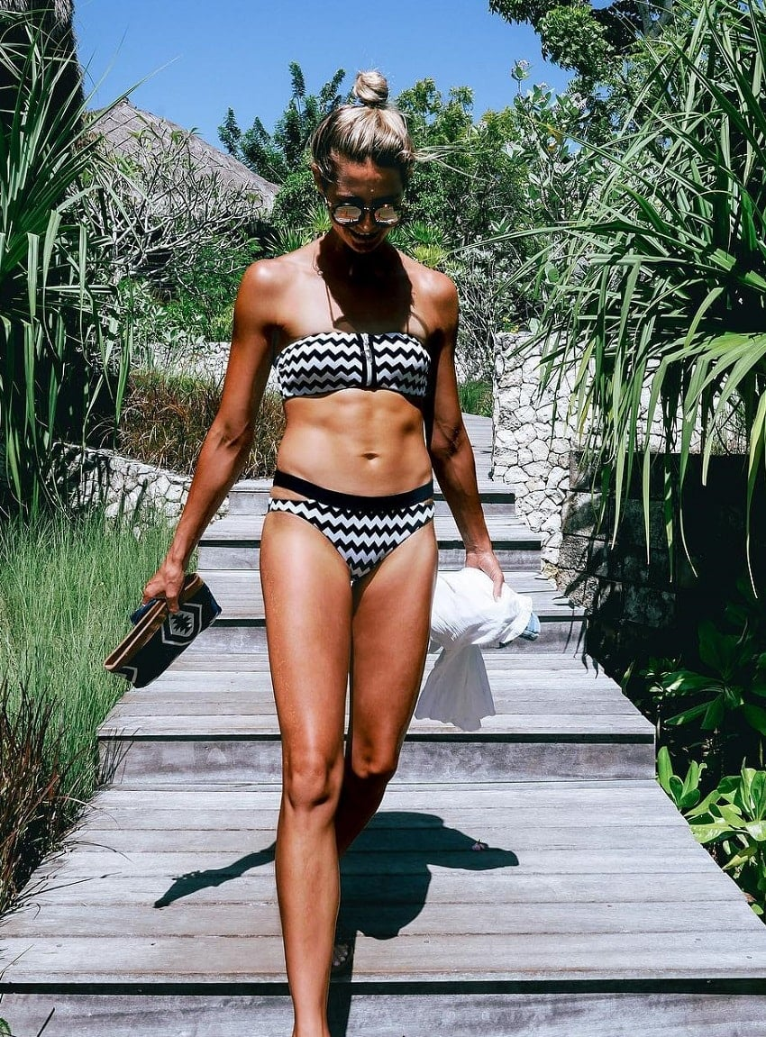 Amanda Bisk walking outdoors in her swimsuit looking lean and fit