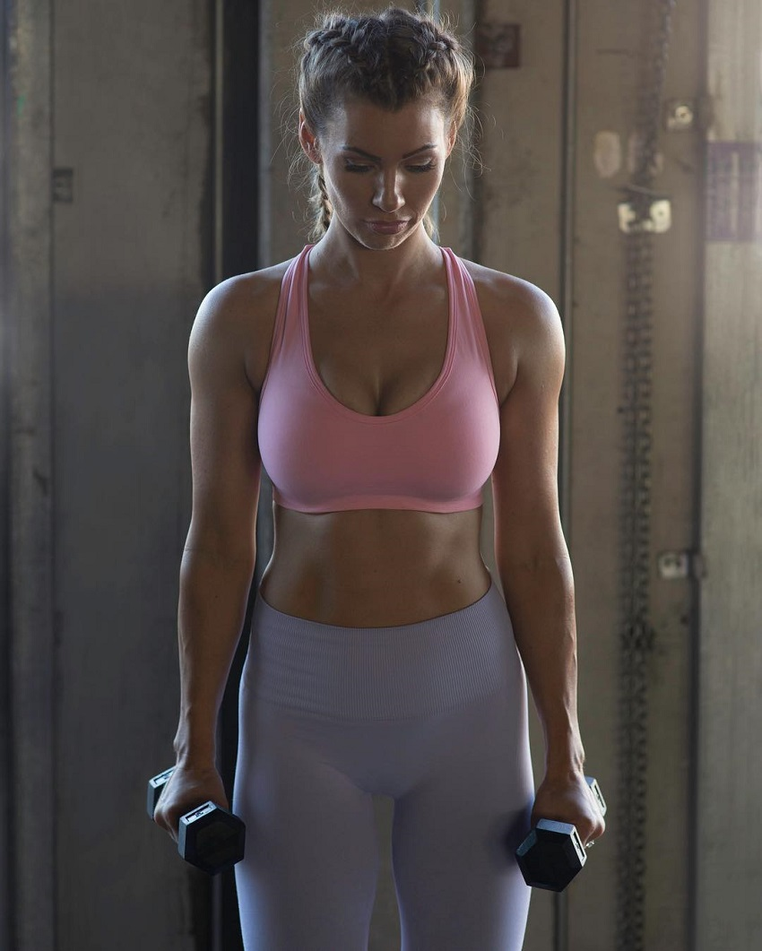 Anna Victoria holding dumbbells wearing a gym sportswear