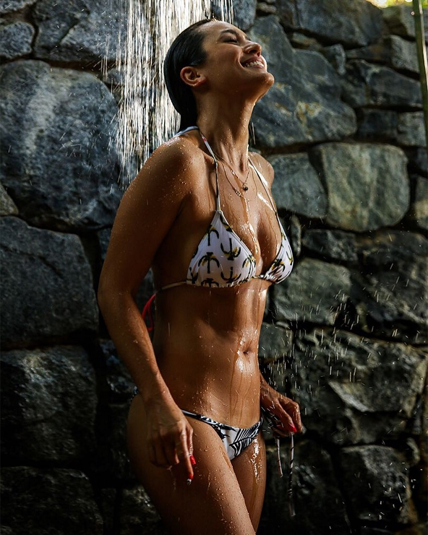 Bianca Cheah standing by a waterfall looking up, her body looking lean and toned