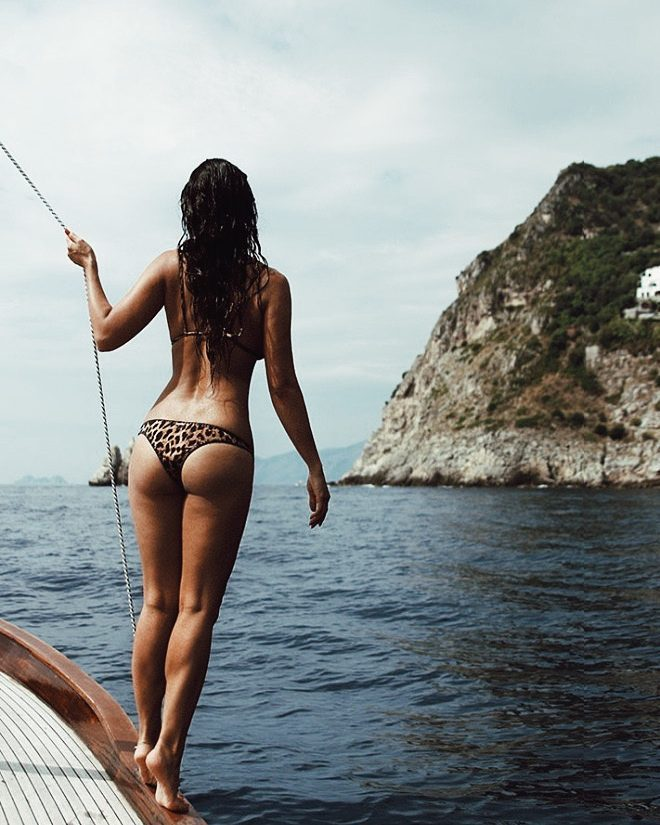 Bianca Cheah standing on a boat in her bikini looking at the sea