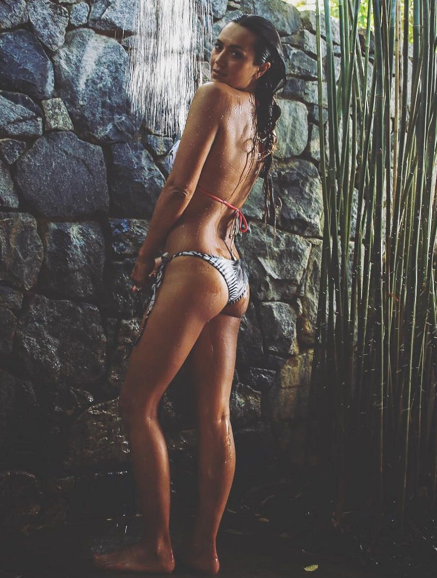 Bianca Cheah standing by a waterfall in her bikini looking fit and lean