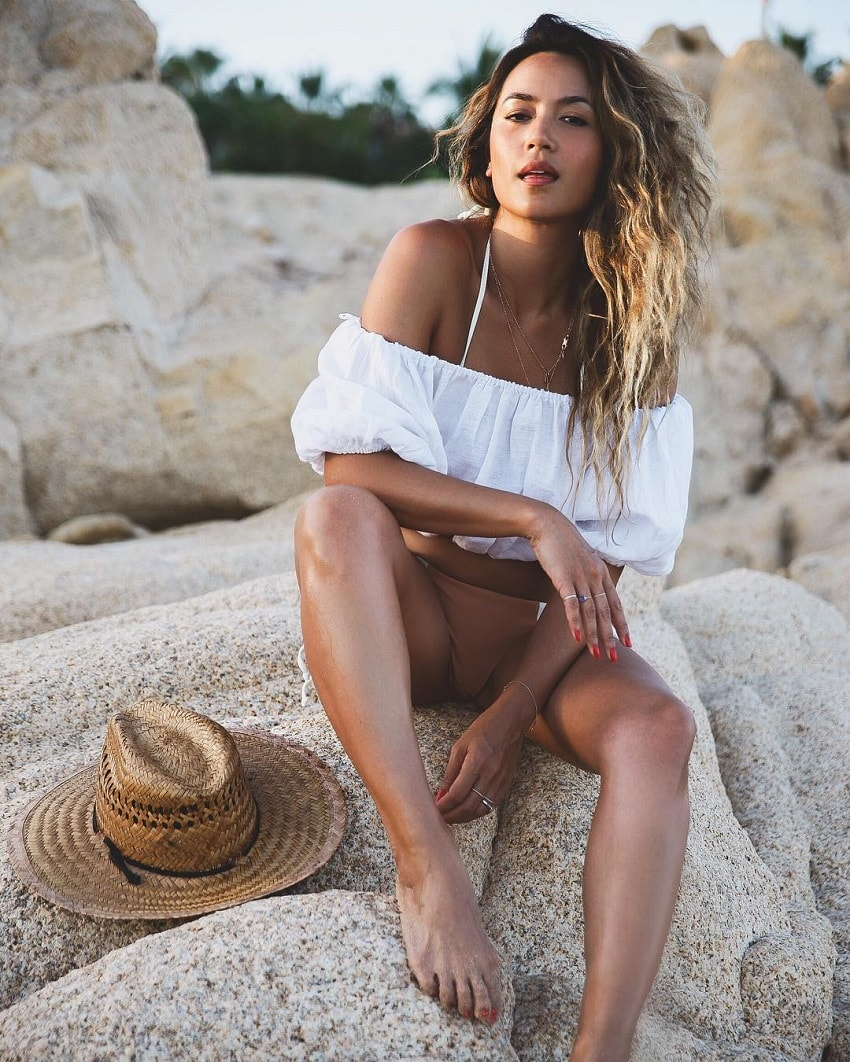 Bianca Cheah sitting on a rock looking fit and lean