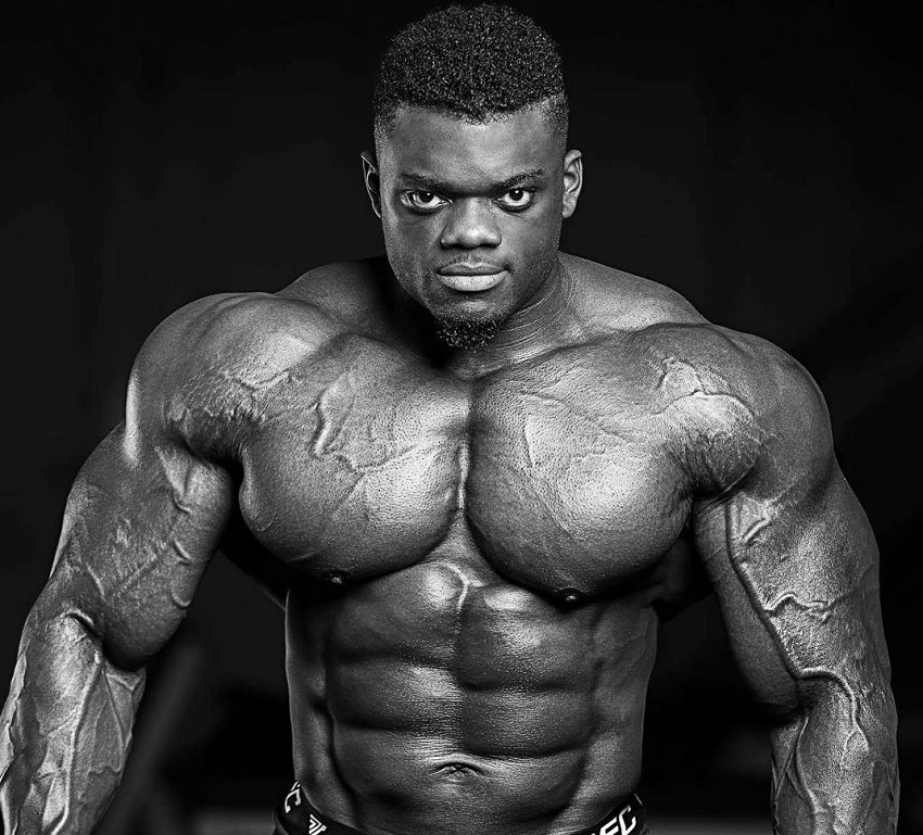 Blessing Awodibu posing shirtless in a photo shoot, looking huge and ripped