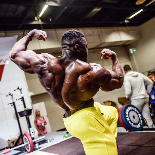 Blessing Awodibu flexing his back and arms in a photo