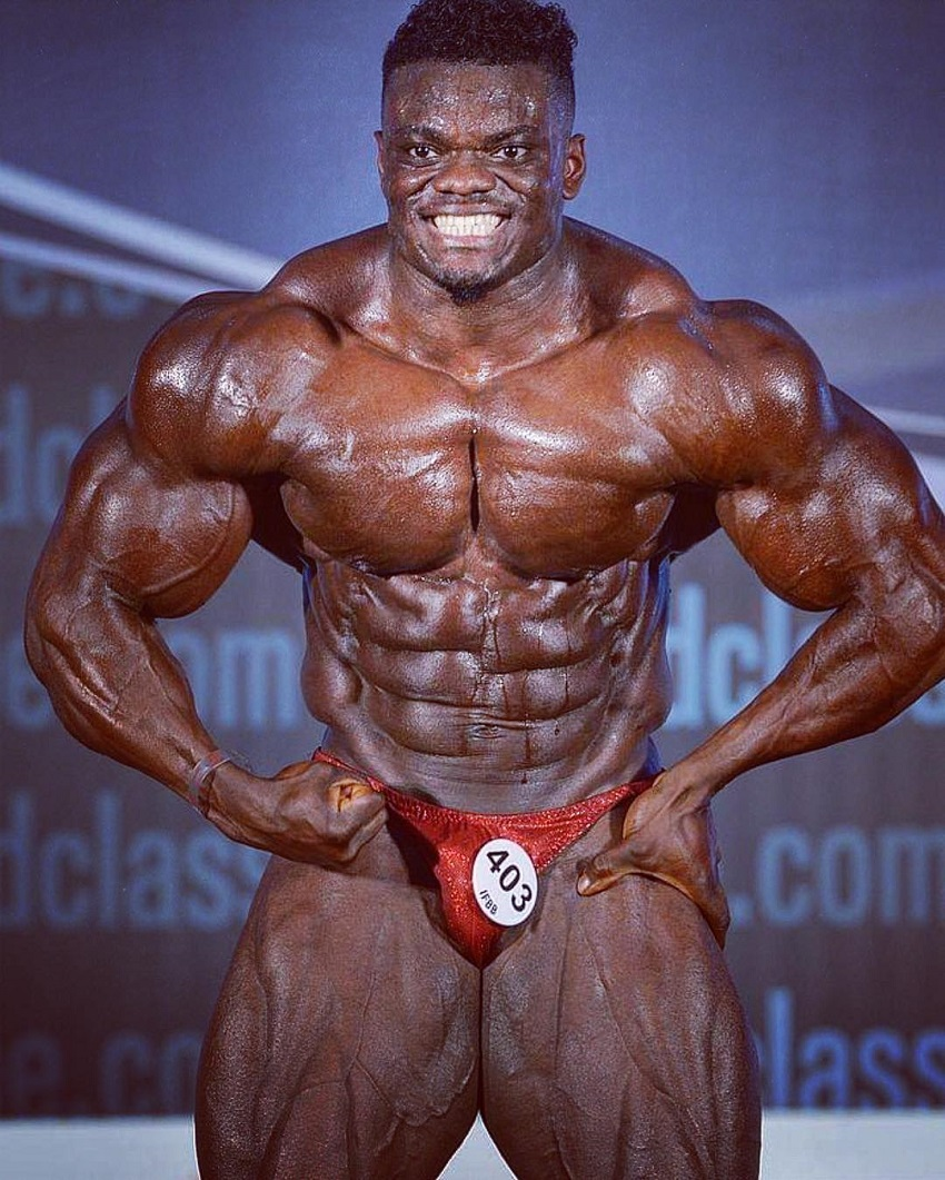 Blessing Awodibu doing a most muscular pose on a bodybuilding stage