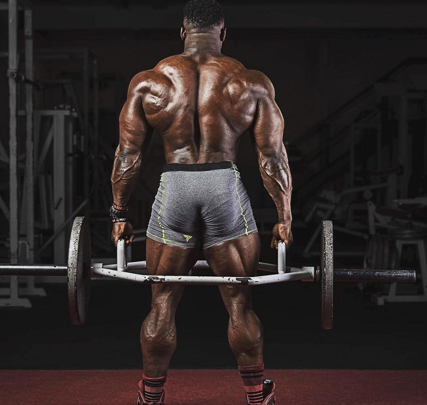 Blessing Awodibu lifting heavy weights in a photo shoot, his back looking big and strong