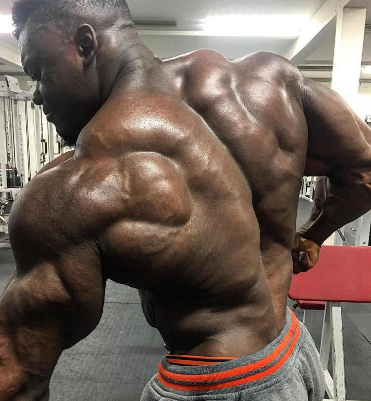 Blessing Awodibu flexing his ripped and huge back in a gym