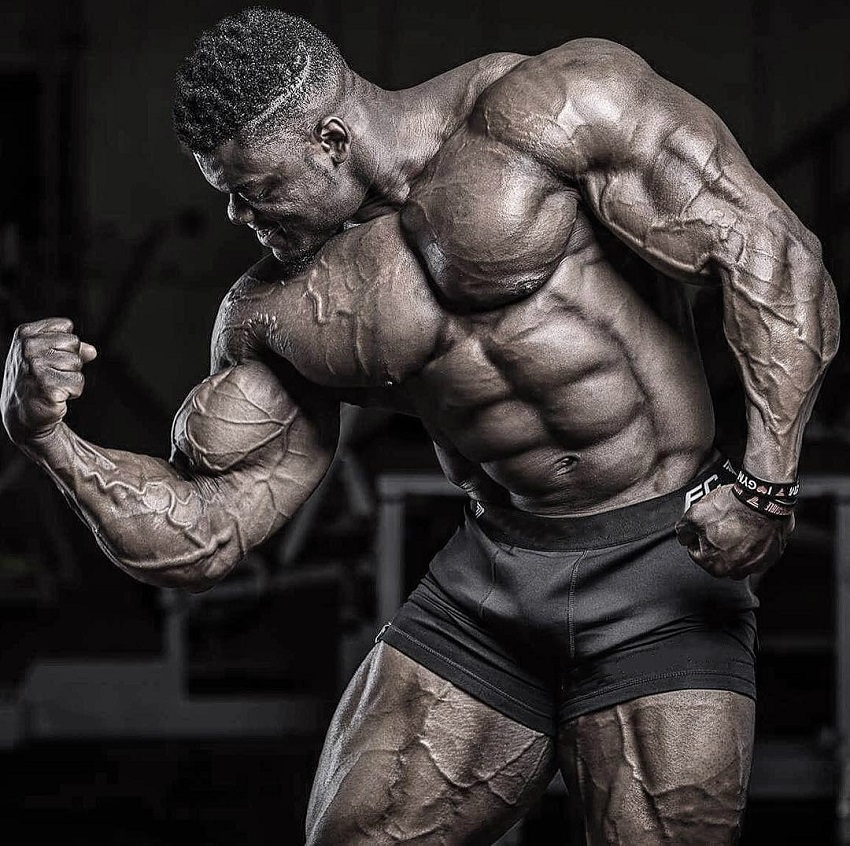 Blessing Awodibu flexing his big and ripped muscles in a professional bodybuilding photo shoot