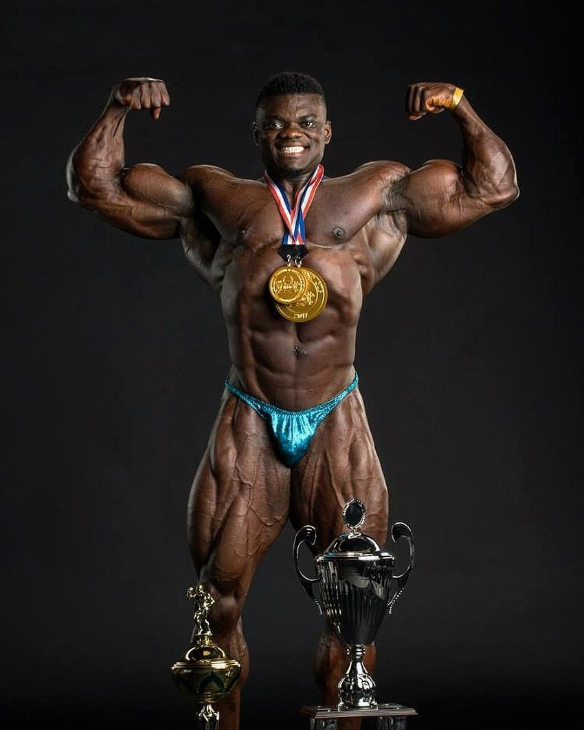 Blessing Awodibu flexing shirtless with his medals and trophies