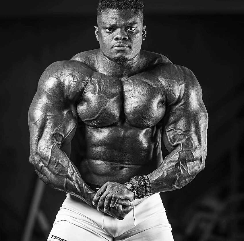 Blessing Awodibu flexing his arms chest and abs in a photo shoot