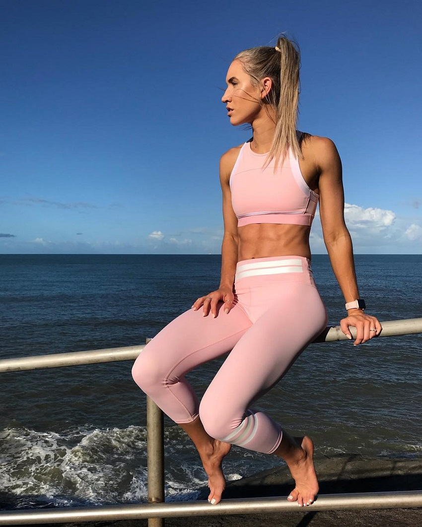 Cass Olholm sitting on a fence by the sea, looking lean and healthy