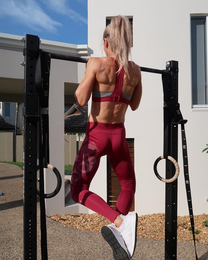 Cass Olholm performing pull-ups looking lean and muscular