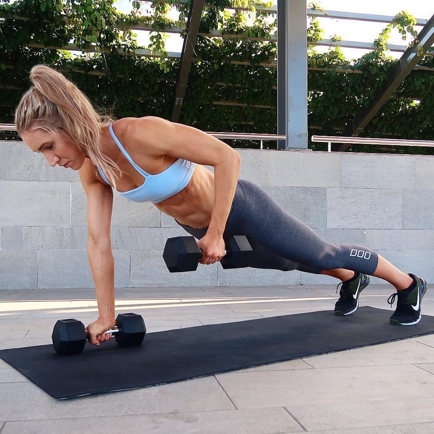 Cass Olholm exercising with a pair of dumbbels on a yoga mat