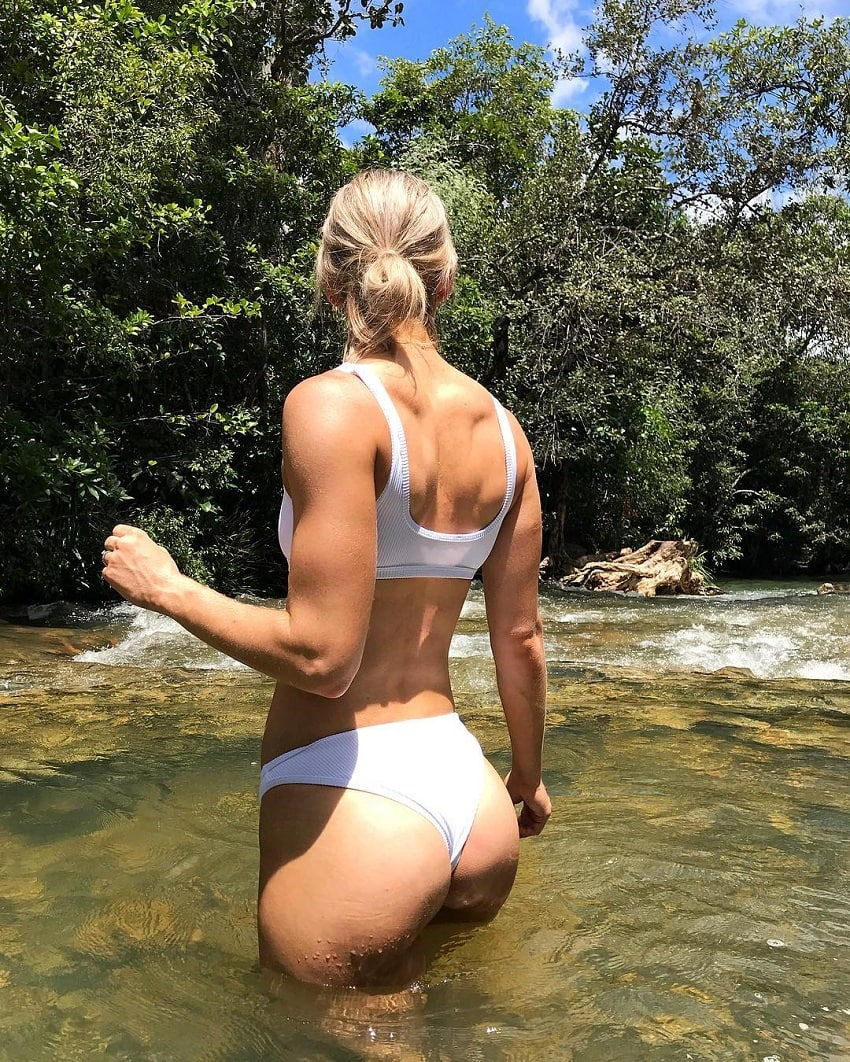 Cass Olholm standing in the river wearing a white bikini