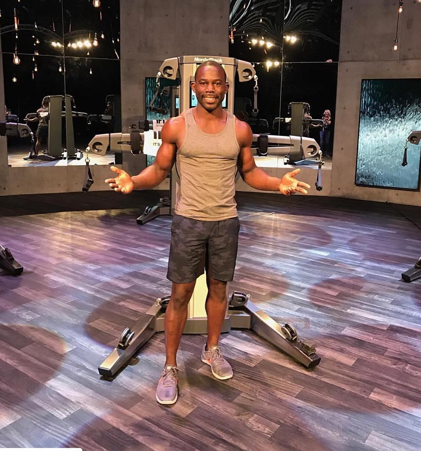 Gideon Akande standing in a grey tank top showing off his lean physique